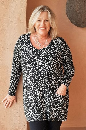 The model in this photo is wearing a patterned black and ecru Tahani tunic from Kasbah Clothing in plus sizes at Bakou