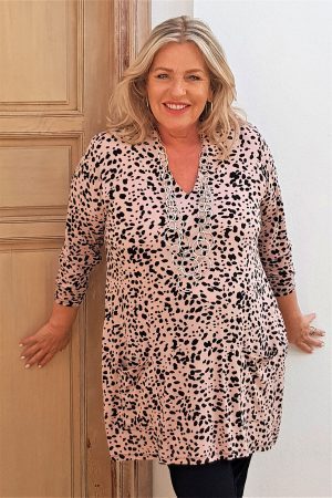 Model is wearing a Kasbah Trea dusty pink animal print jersey tunic with a deep v neck